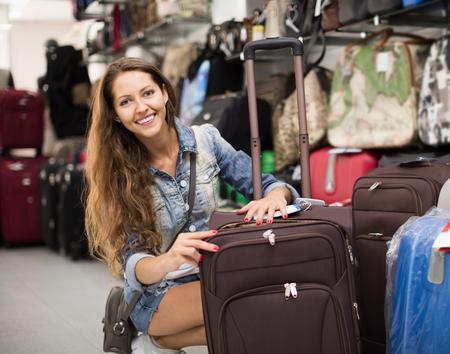portmanteau: smiling  woman choosing luggage bag in shop Stock Photo