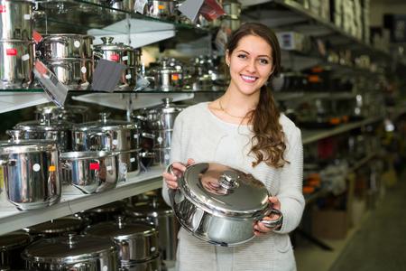 cookware: Mujer que compra en la tienda de utensilios de cocina de la cacerola
