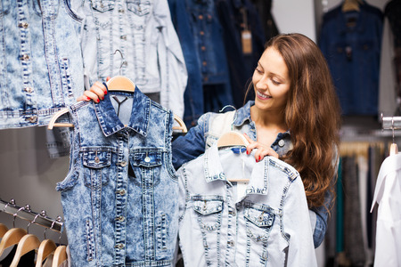 coatee: Young smiling girl buying jacket in clothing store
