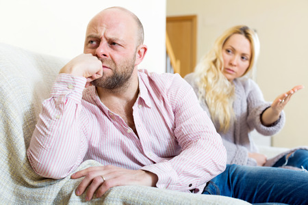 Family quarrel. Sad adult  guy and young woman during quarrel  in living room at house  couple having problems at home Stock Photo