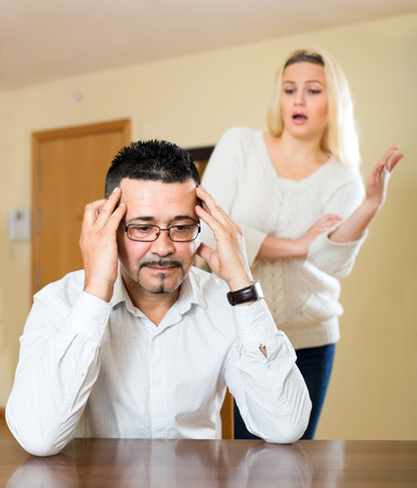 Wife nagging her husband which is sitting at the table in a living room holding his head with his hands