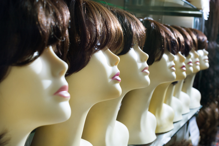 peruke: Dummies heads with modern hair style periwigs at the shop Stock Photo