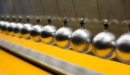 impulse: Line of metallic globes for Cartesian impulse conservation law experiment Stock Photo