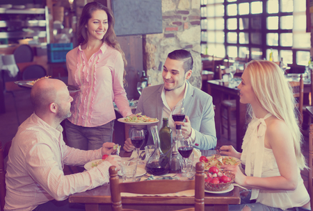 respectful: Portrait of relaxed people having dinner and respectful waiter