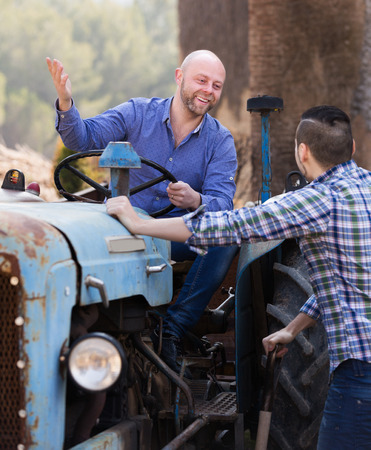 sucessful: Two smiling male drivers working with tractor and chatting outdoor Stock Photo