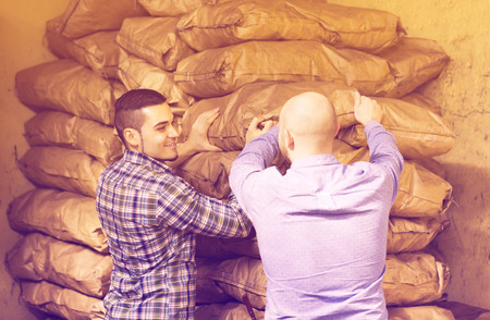 stockpiling: Two young positive loaders handling sacks with something heavy indoors
