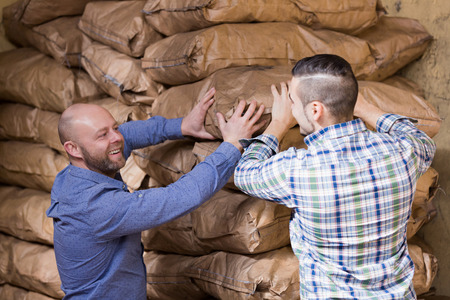 stockpiling: Strong happy russian workmen unloading shed with coal bags Stock Photo