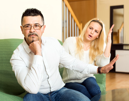 jackboot: Wife is having a quarell with her husband over his job and salary. She is talking loudly while he is sitting turned away from her tired Stock Photo