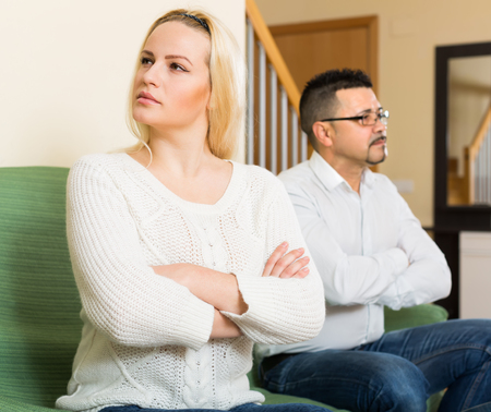 adultery: Family quarrel. Sad husband and his angry wife during quarrel in living room at home Stock Photo
