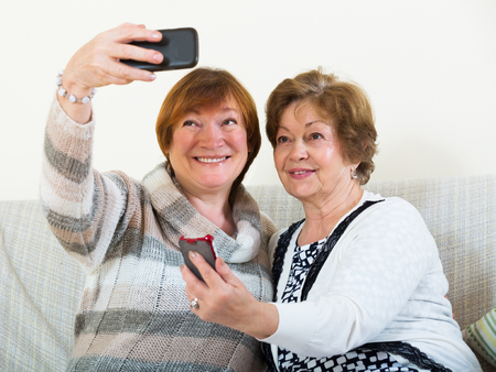 75s: Happy female pensioners making selfie on phone and smiling at home