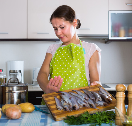 Young housewife in apron cooking fish and wincing of disgusting smell Stock Photo