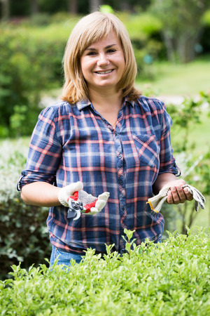 horticultural: smiling blond mature woman  holding horticultural tools in garden on sunny day Stock Photo
