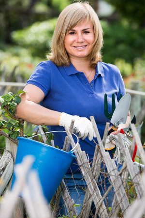 horticultural: happy smiling  blond mature woman standing in garden with horticultural instruments on summer day Stock Photo