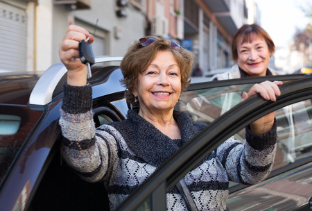 golden age: smiling female driver in golden age standing with car key outdoor