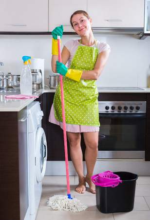 Young housewife in apron washing floor in domestic kitchen