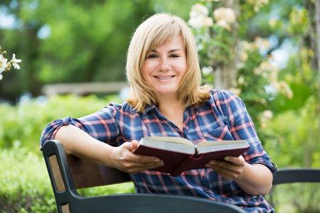 closeup portrait of glad blond mature woman enjoying her book in garden on summer day