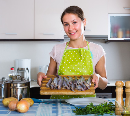 loathsome: Portrait of smiling woman in apron preparing small fish in the kitchen