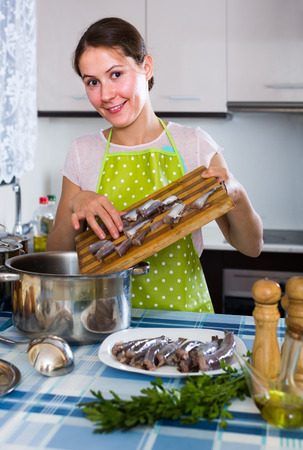 Happy american housewife trying new recipe of sprattus in kitchen