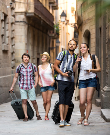itinerary: Group of cheerful young tourists with map and camera outdoors