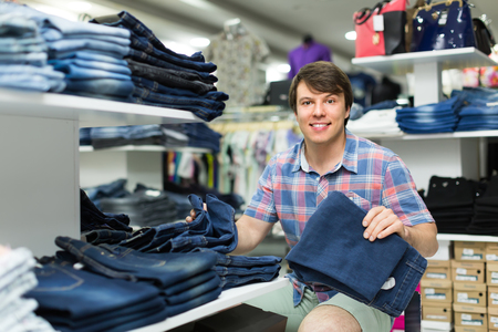 levis: Happy smiling man choosing new pair of blue jeans at the shop