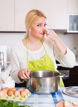 Woman takes lid off pan and feel musty smell at home kitchen Stock Photo