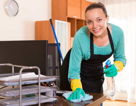 Cheerful smiling female cleaner making cleaning in the office-room Stock Photo