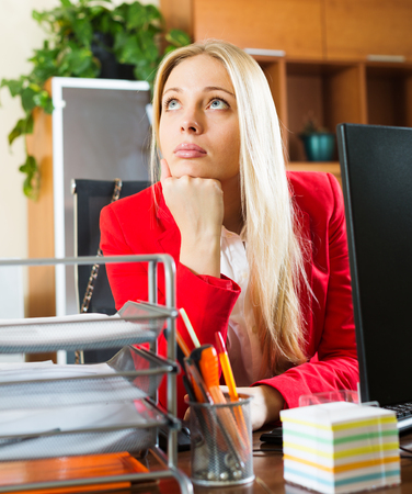 unprofessional: Bored businesswoman in red sitting at office  and dreaming