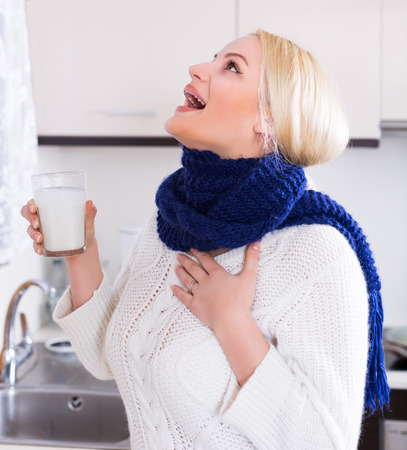 Young woman standing near sink with gargle solution Stock Photo