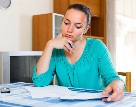lamentable: Tired young woman filling out tax forms while sitting at her desk