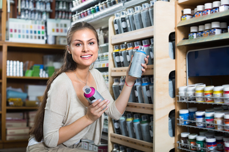 aerosol can: portrait of joyful smiling young woman choosing paint color in aerosol can in art shop
