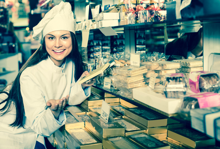 shopgirl: Young shopgirl posing with delicious chocolate and candies at display