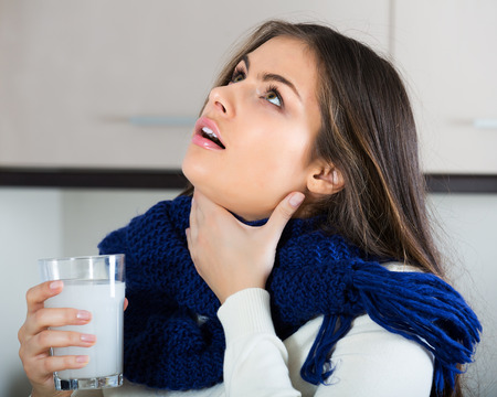 Young brunette woman in scarf gargling throat with medicine 스톡 콘텐츠