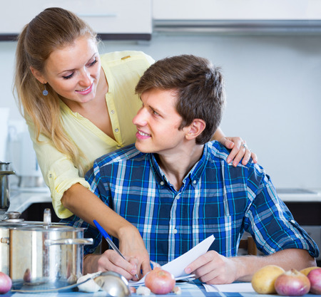 spouses: Happy spouses filling forms for joint banking account at kitchen Stock Photo