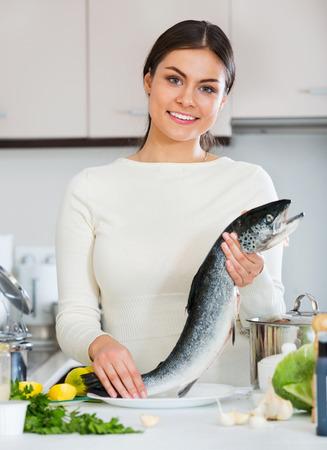 jorobado: Atractiva joven morena chica preparar plato de trucha para la cena sana
