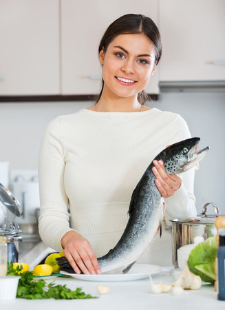 jorobado: Attractive Young brunette girl preparing trout dish for healthy dinner
