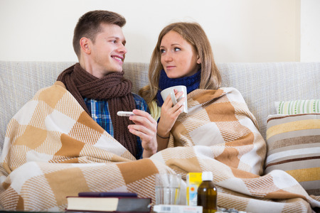 flue: Spouses having flue together, sitting with thermometer and tea Stock Photo