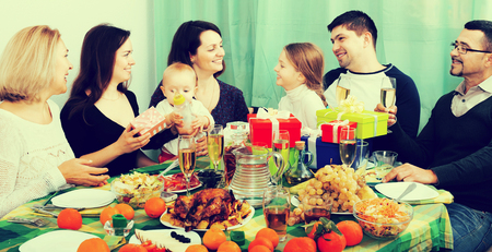relatives: Smiling relatives wishing little girl happy birthday and giving presents at festive table. Focus on girl
