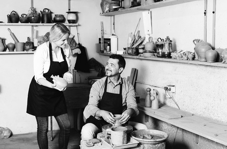 two wheel: portrait of two joyful smiling potters working with pottery wheel in ceramics atelier