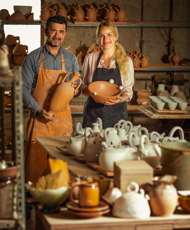 artisans: Two cheerful artisans in aprons having ceramics in hands and standing in workshop