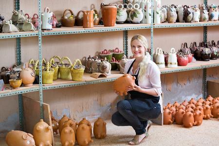 diligente: Portrait of  smiling diligent woman pottery worker with ceramic crockery in hands in studio Foto de archivo