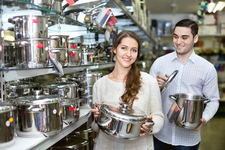 cookware: Pares alegres jovenes en la sección de utensilios de cocina en el hipermercado Foto de archivo