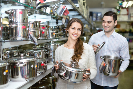 cookware: Young cheerful  couple in the cookware section at hypermarket Stock Photo