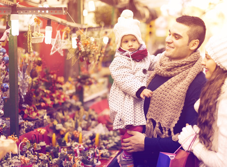 5s: Happy married couple with two children choosing Christmas decorations at market.