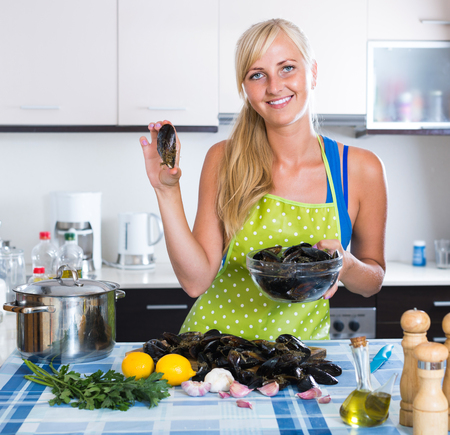 kitchen spanish: Young happy spanish  woman cooking marinade for tasty mussels at kitchen table