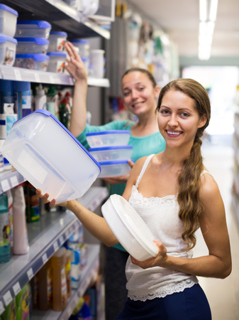 Adult woman in good spirits selecting pails at store