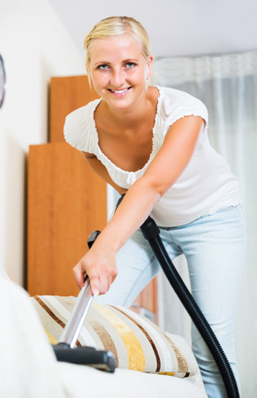 Cheerful young housewife in jeans vacuuming floor and furniture