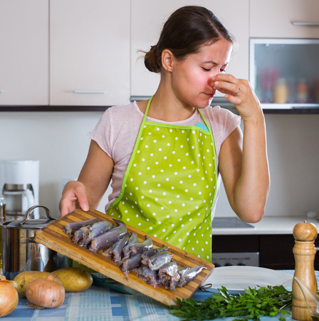 Housewife in apron wincing of disgusting smell of fish at kitchen Stock Photo