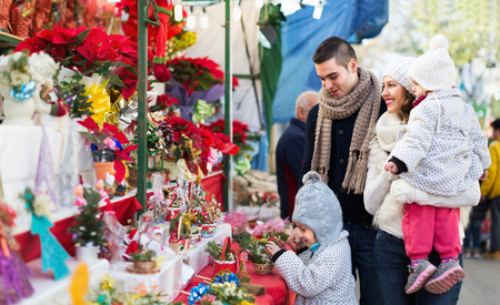 Smiling parents and happy children buying red Euphorbia at Christmas fair. Focus on woman