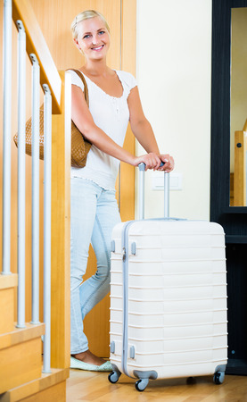 Smiling blonde young girl standing with luggage near entrance indoors