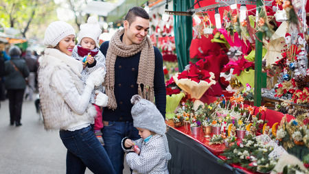 Positive mother, father and children buying red Euphorbia at Christmas fair. Focus on man